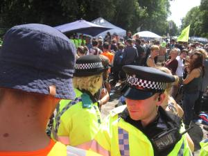 Police lines contain protestors outside the site entrance
